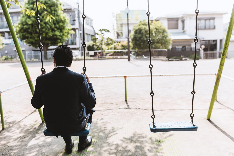 公園のブランコで時間を潰す後ろ姿が切ないビジネスマン
