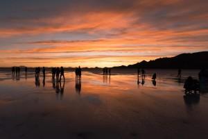 美しい夕暮れのウユニ塩湖と観光客のシルエット
